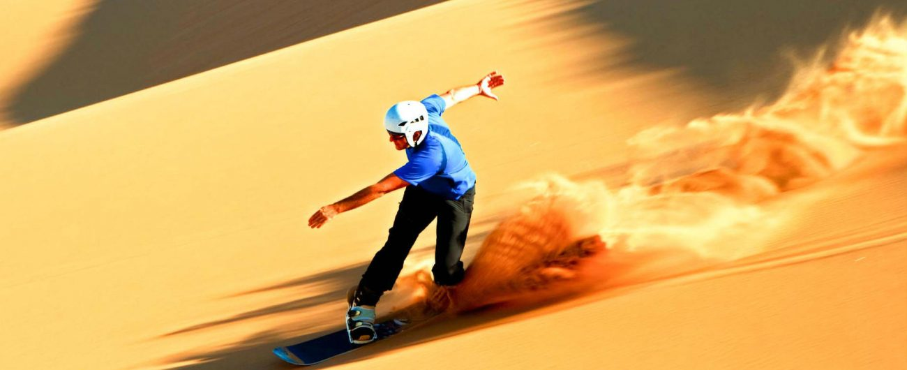 Sand boarding down the slopes