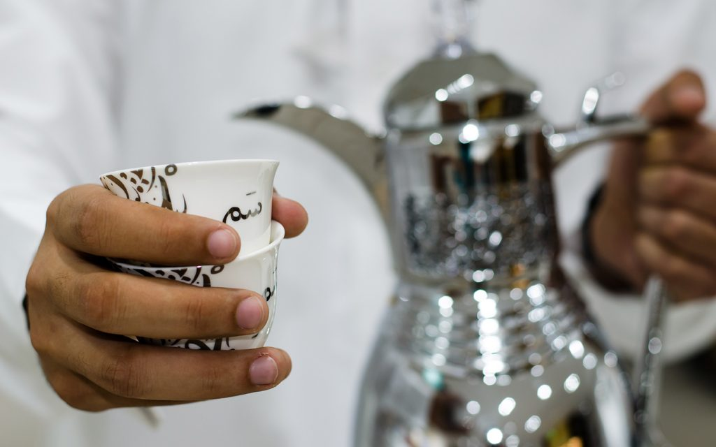 Arab holding coffee cup
