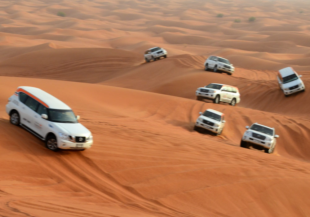 A fleet of cars following a convoy at the time of dune bashing in the Desert