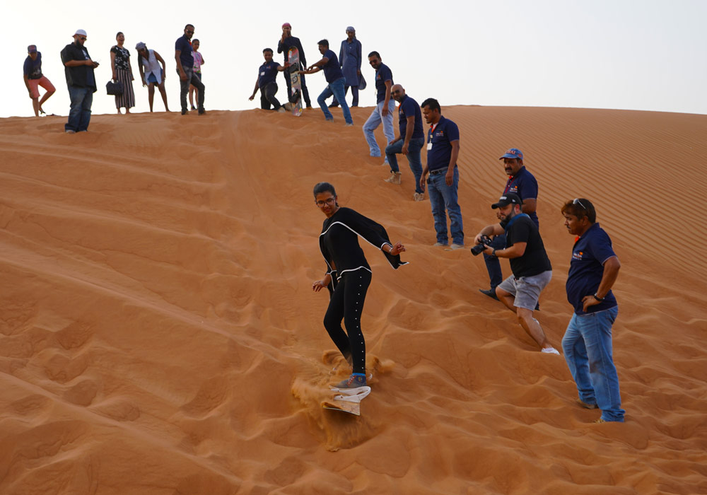 Learning to sand-board in the middle of Dubai desert with the help of safari guides